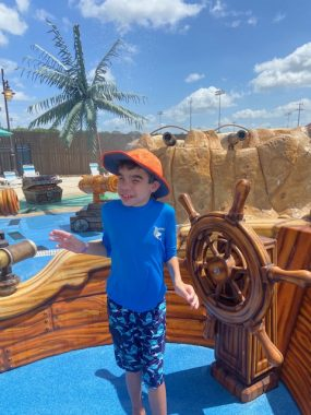 Inclusive spaces and summertime caregiving | Sanfilippo News | Columnist Valerie Tharp Byers 11-year-old son, Will, enjoys a day at the ultra-accessible water theme park Morgan's Wonderland. Will, wearing an orange sun cap and light blue shirt, poses in front of a pirate-ship-themed attraction