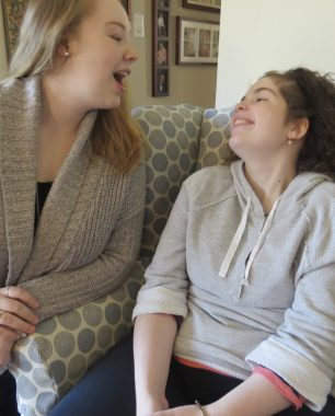communication \ Sanfilippo Syndrome News \ Columnist Emily Wallis and her sister, Abby, sit on a living room chair and share a funny exchange in an older photo, before Abby lost her ability to verbally communicate.