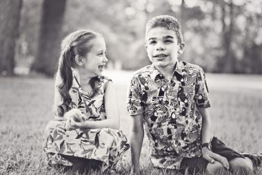 parenting children with Sanfilippo | Sanfilippo Syndrome News | Will's younger sister looks at her brother as they sit in the grass in this stunning black-and-white photo with short depth of field and stunning light